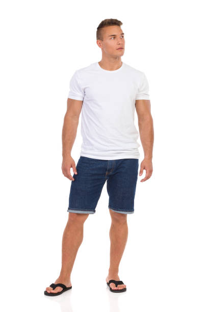 casual man in white t-shirt and jeans shorts looking away - jean shorts stock photos and pictures
