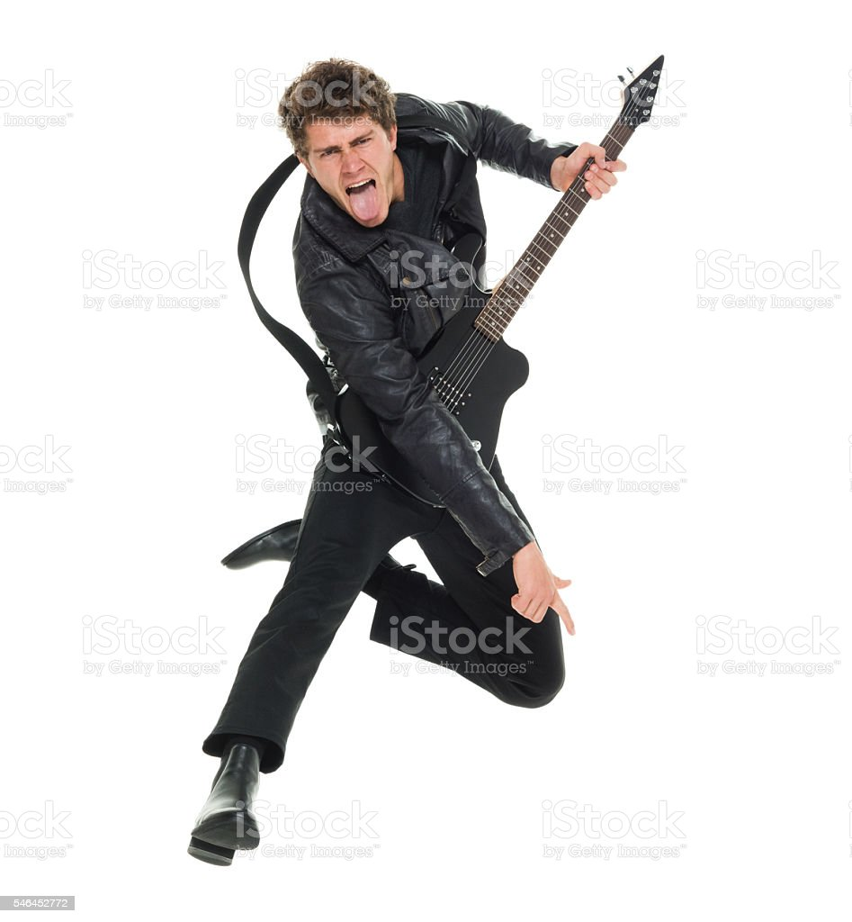 Casual man jumping and playing guitar stock photo