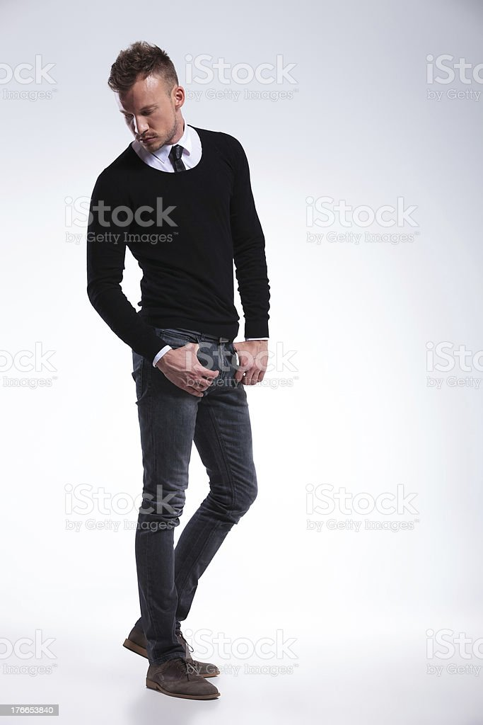 casual man looks down with thumbs in pockets royalty-free stock photo
