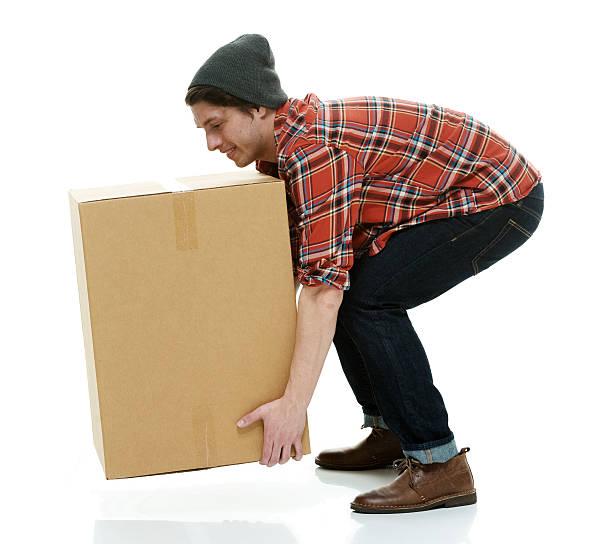 Casual man picking up box stock photo