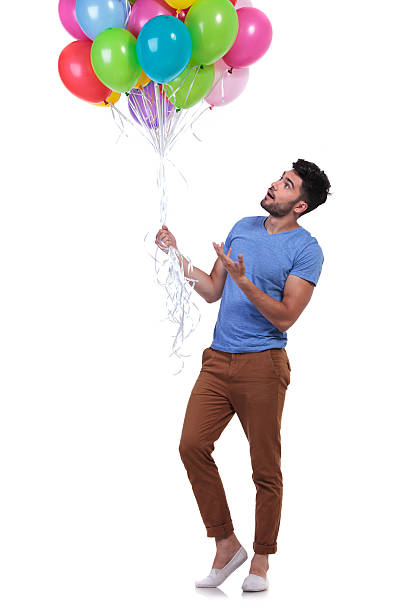 legerer mann präsentieren einen haufen bunte ballons - ballonhose stock-fotos und bilder