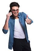 Smiling casual man showing the thumbs up gesture while talking on the phone