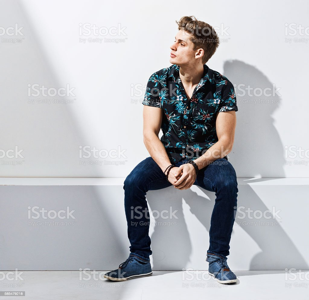 Casual man sitting and looking away stock photo