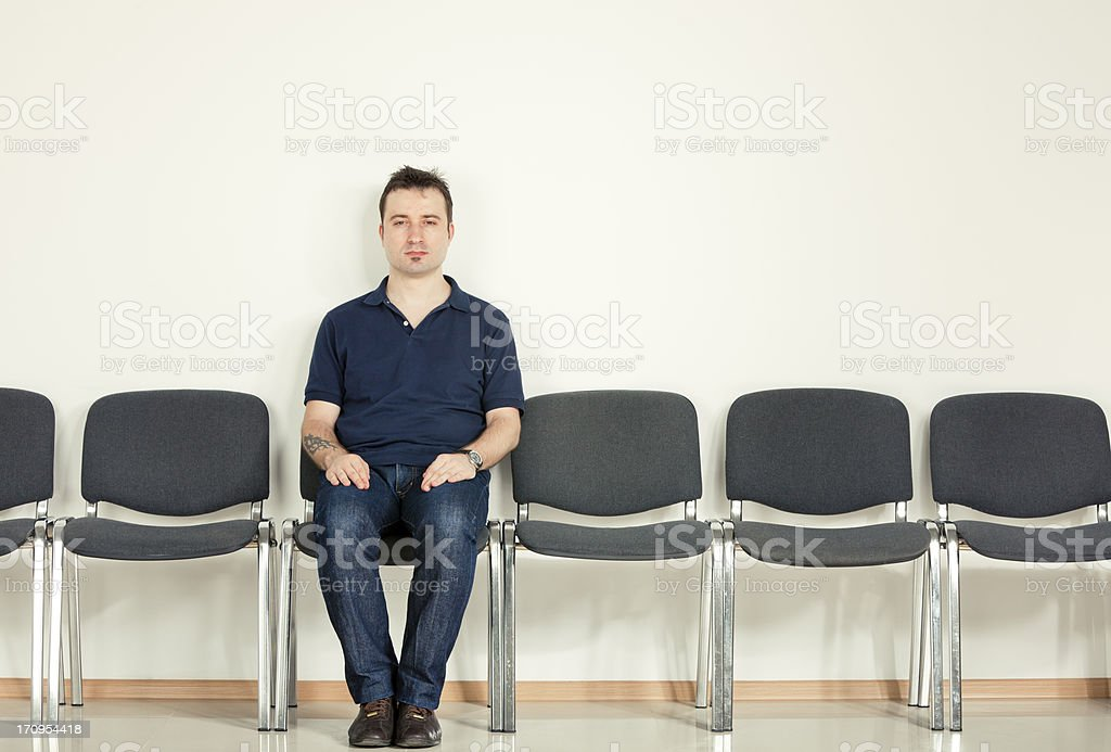 Casual man sitting on row of chairs stock photo