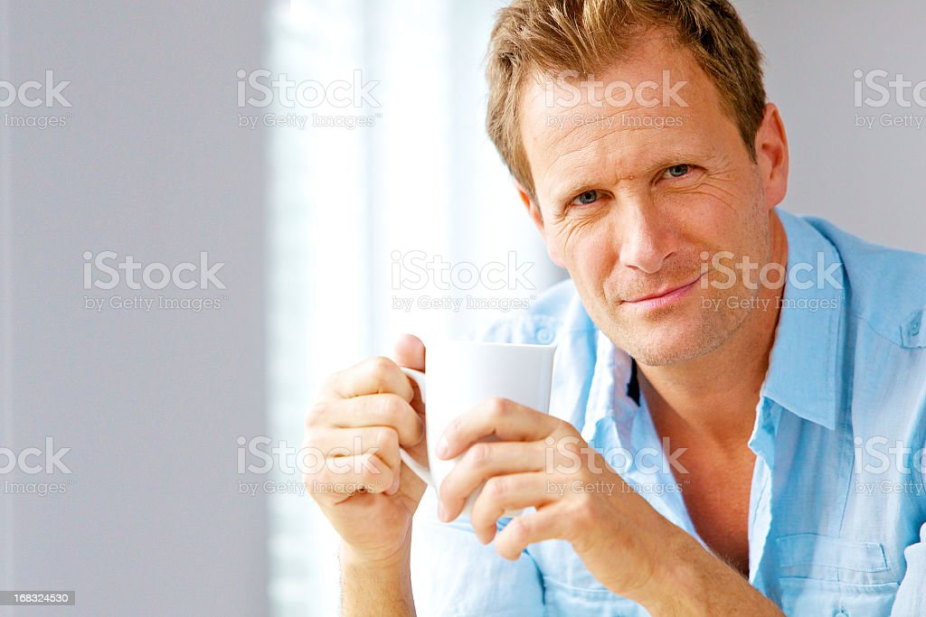 Casual man smiling and drinking coffe royalty-free stock photo