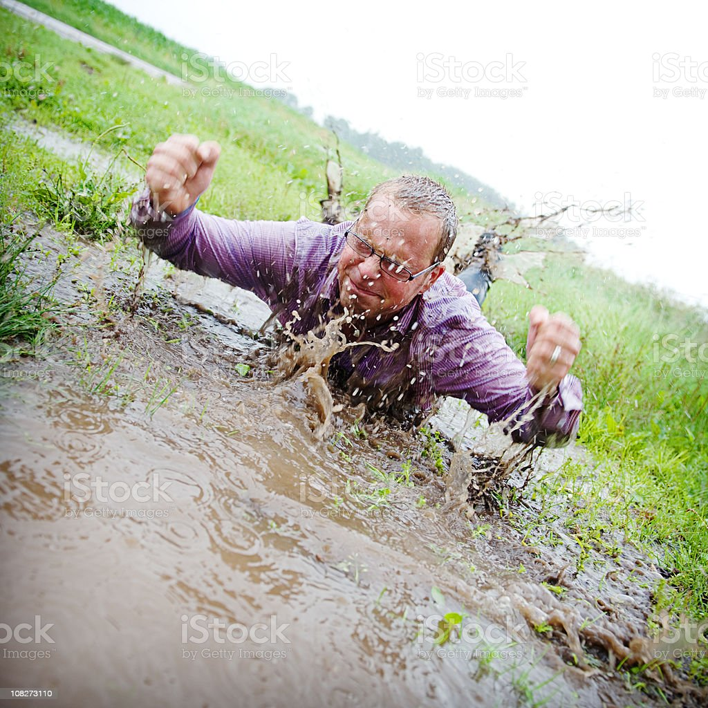 Casual man splashing in a puddle with mud royalty-free stock photo