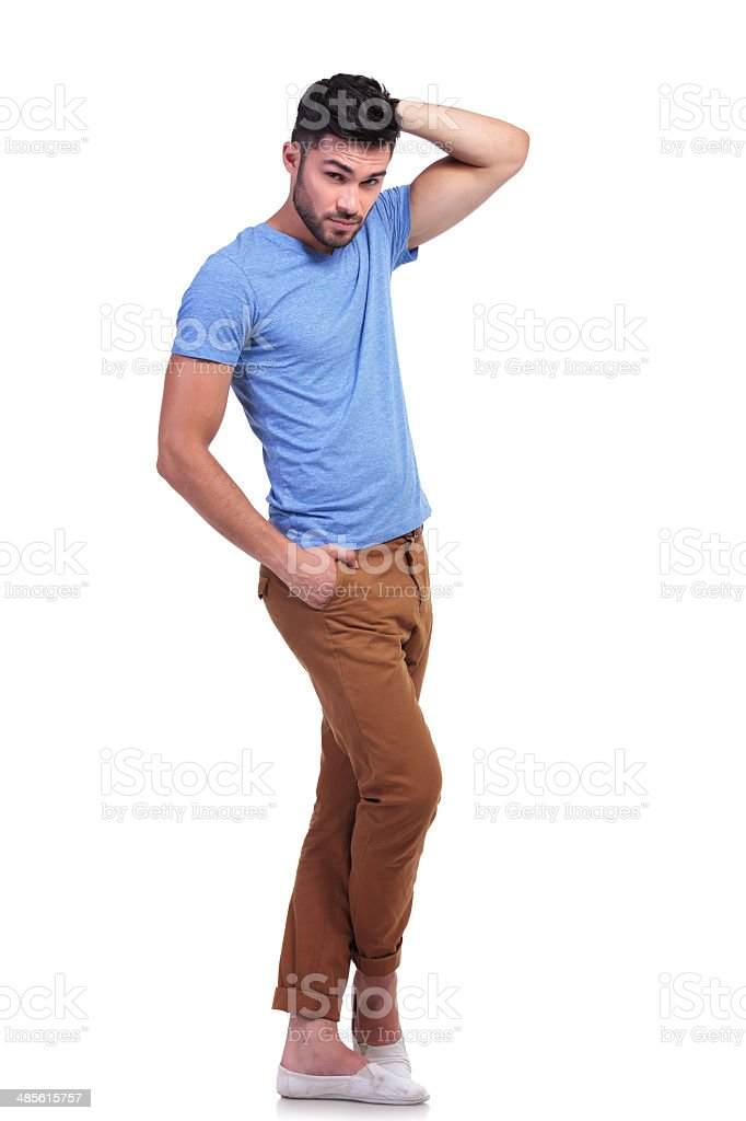 casual man standing with hand on head stock photo