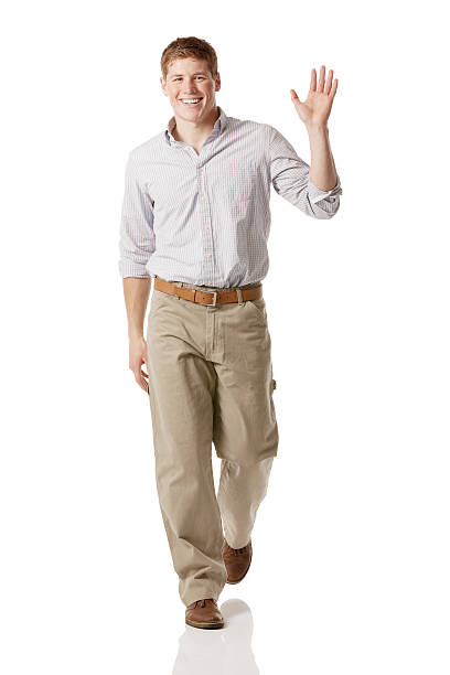 casual man walking and waving hand - waving stock photos and pictures