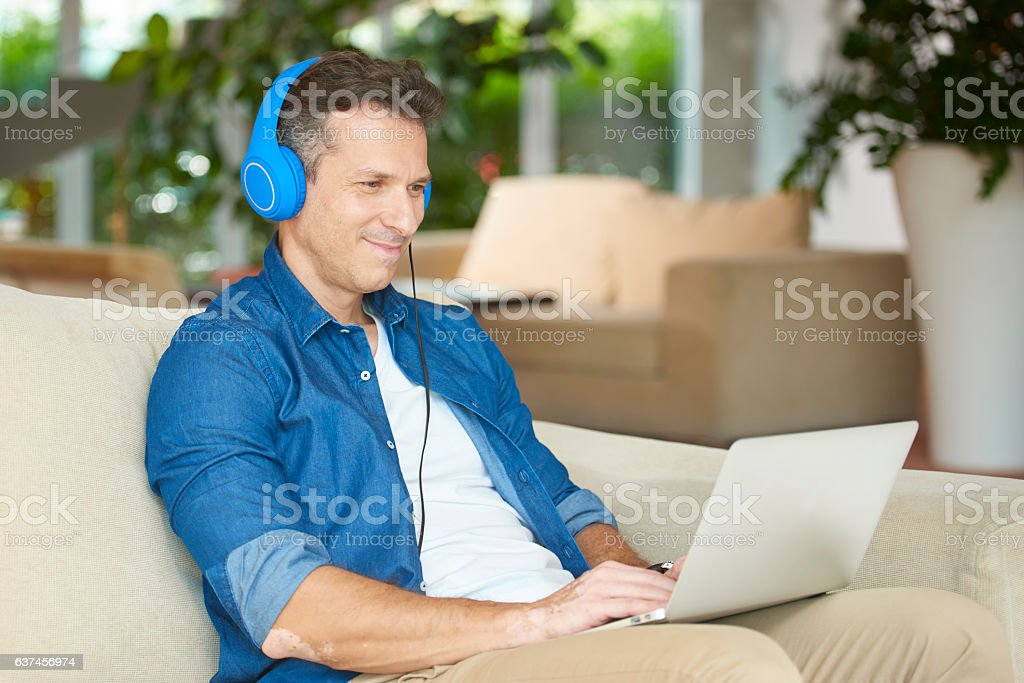 Casual man with laptop at home stock photo