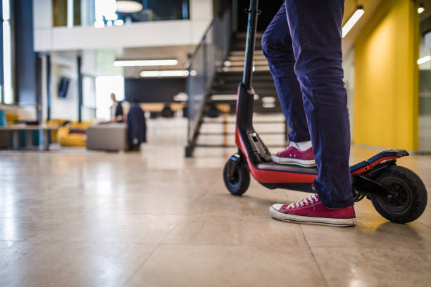 casual manager arriving to the office on his electric scooter - electric push scooter stock photos and pictures