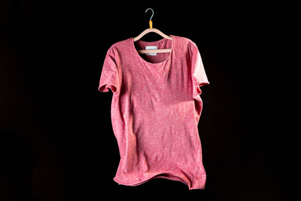 casual men t-shirt on a hanger on the dark background mockup copy space stock photo