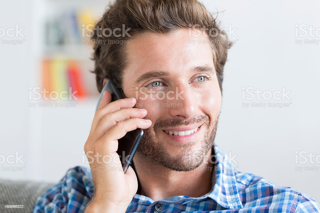 Casual mid adult man on phone in modern apartment stock photo