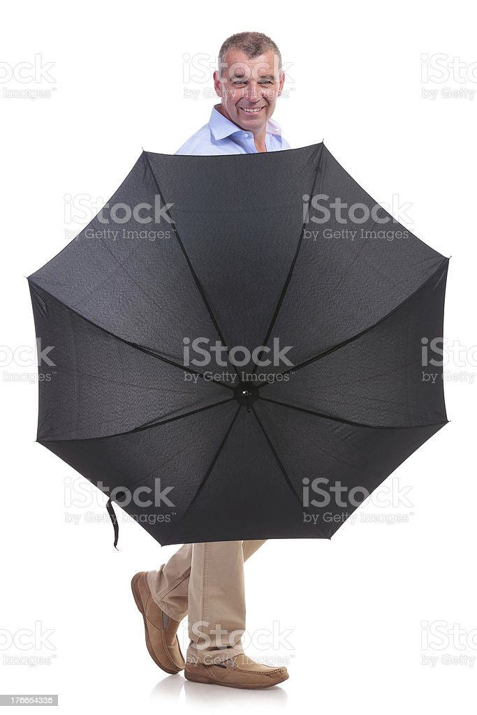 casual middle aged man behind an umbrella royalty-free stock photo