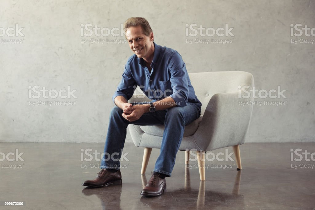 casual middle aged man smiling while sitting on armchair indoors stock photo