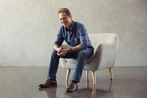 Casual Middle Aged Man Smiling While Sitting On Armchair