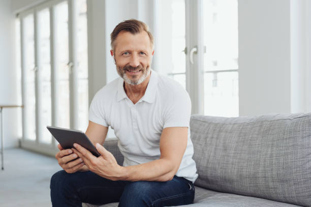 Casual middle-aged man relaxing at home stock photo