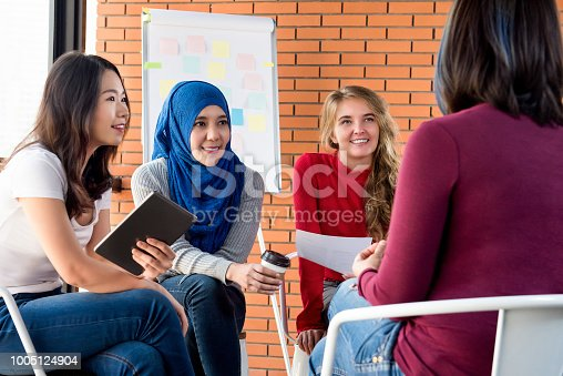 Group of diverse women in casual colorful clothes sitting in circle meeting for social project