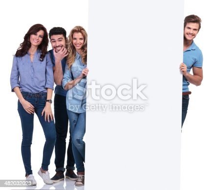 istock casual people fooling around and presenting a blank board 482032023
