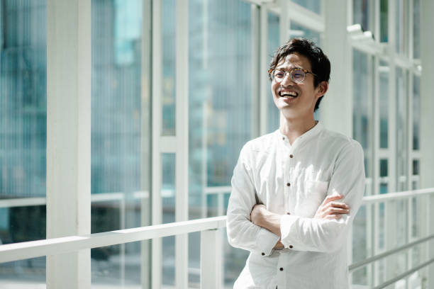 Casual portrait of a young Asian business person Casual business portrait of a young Asian man standing by the window. Looks like a CEO or engineer. japanese ethnicity stock pictures, royalty-free photos & images