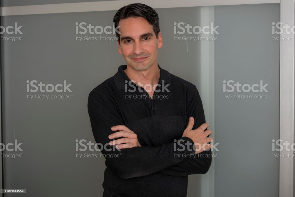 Casual portrait of Hispanic business man smiling inside office....