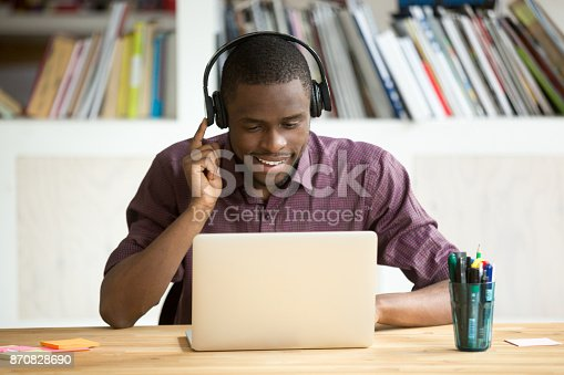 istock Casual smiling office worker in headphones looking at laptop screen. 870828690