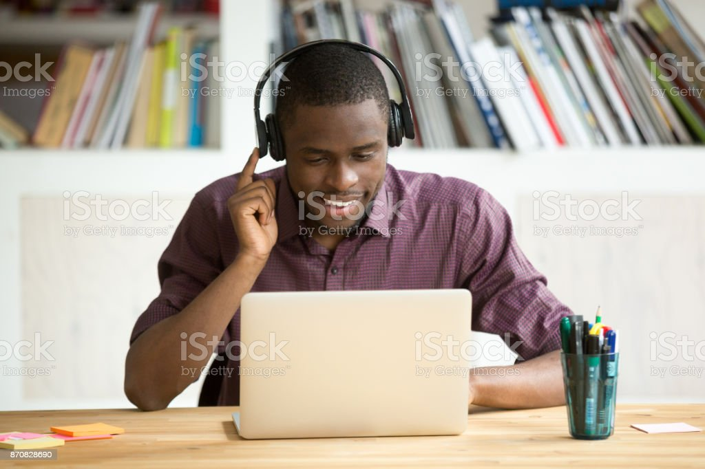 Casual smiling office worker in headphones looking at laptop screen. stock photo