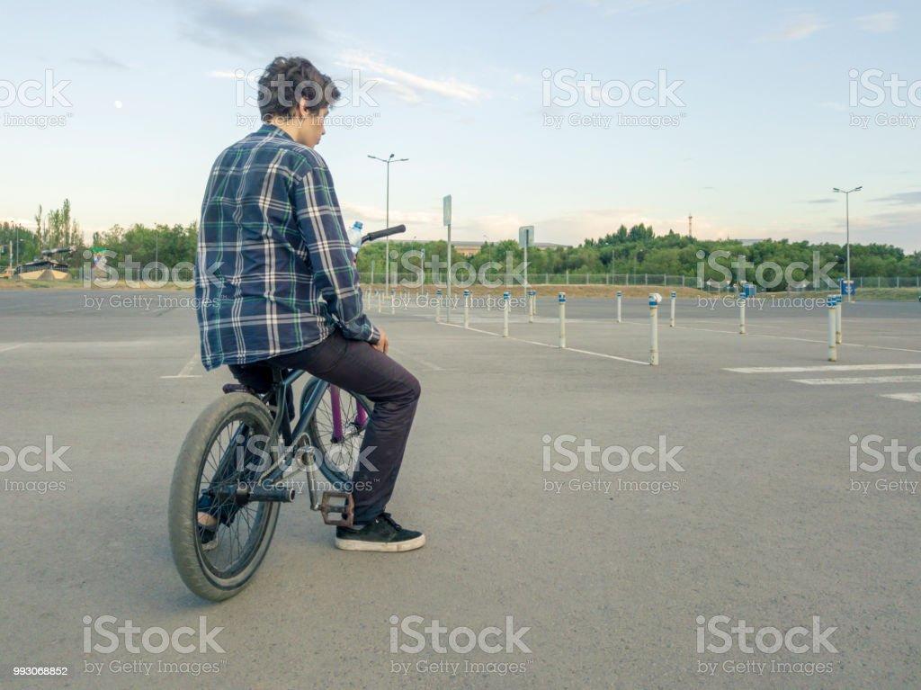 casual teenage boy sitting chilling on bike on large asphalt sports ground stock photo