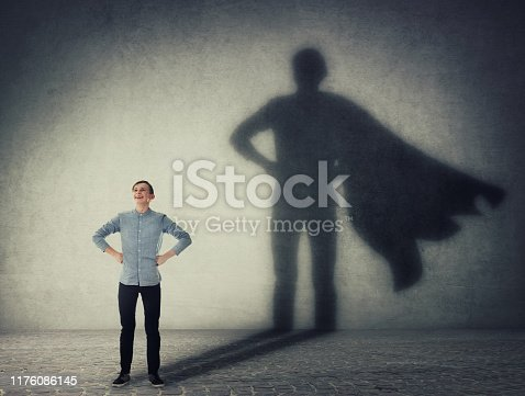 istock Casual teenage, keeps arms on hips smiling confident, casting a superhero with cape shadow on the wall. Student ambition success concept. Leadership hero power, motivation and inner strength symbol. 1176086145