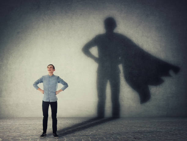 Casual teenage, keeps arms on hips smiling confident, casting a superhero with cape shadow on the wall. Student ambition success concept. Leadership hero power, motivation and inner strength symbol. Casual teenage, keeps arms on hips smiling confident, casting a superhero with cape shadow on the wall. Student ambition success concept. Leadership hero power, motivation and inner strength symbol. heroes stock pictures, royalty-free photos & images