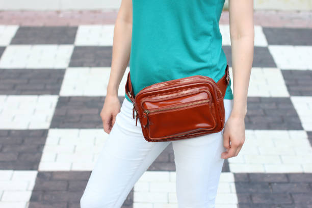casual weared women with big leather weist bag on black and white checkers background. trendy urban accessorys - waist bag stock photos and pictures