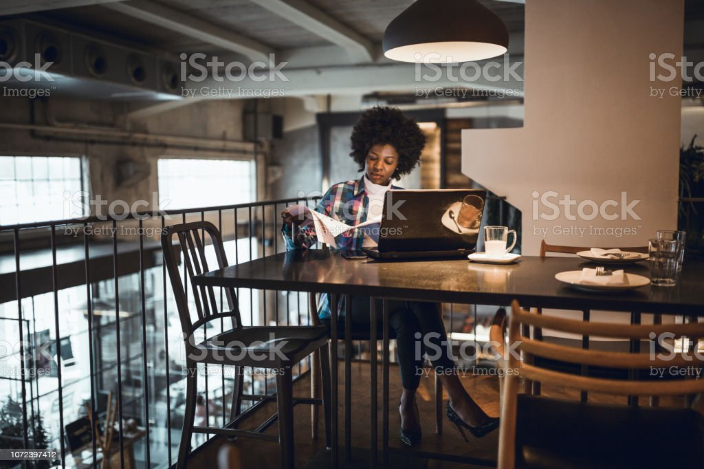 Casual woman, African-American Ethnicity, working at laptop in cafe.