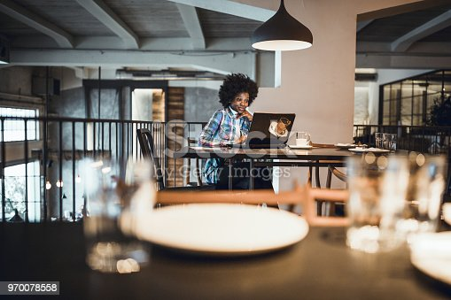 istock Casual woman, African-American Ethnicity, working at laptop in cafe. 970078558