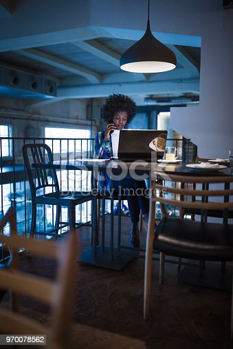 istock Casual woman, African-American Ethnicity, working at laptop in cafe, using mobile phone. 970078562