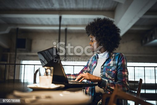 istock Casual woman, African-American Ethnicity, working at laptop in cafe. 970078588