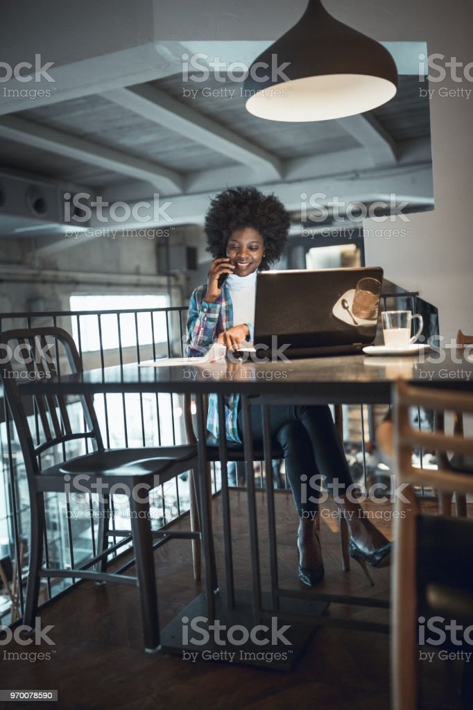 Casual woman, African-American Ethnicity, working at laptop in cafe,...
