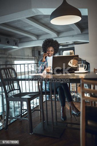 istock Casual woman, African-American Ethnicity, working at laptop in cafe, using mobile phone. 970078590