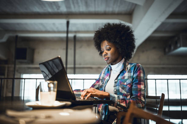 Casual woman, African-American Ethnicity, working at laptop in cafe. stock photo