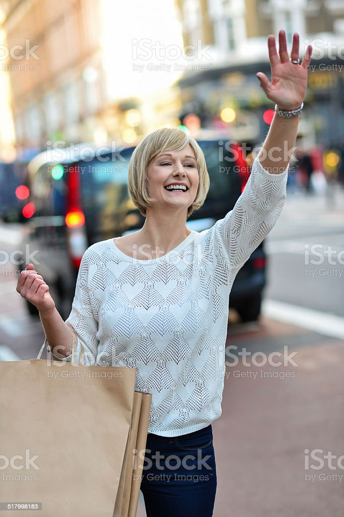 Casual woman hailing a taxi cab royalty-free stock photo