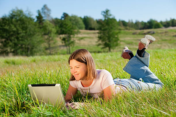Casual Woman in the Grass with Computer stock photo