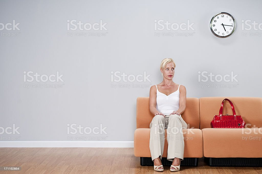 Casual Woman In Waiting Room Casual blonde woman in pants and red purse, waiting in empty room.Take a look at my lightbox of other related images. Waiting Room Stock Photo