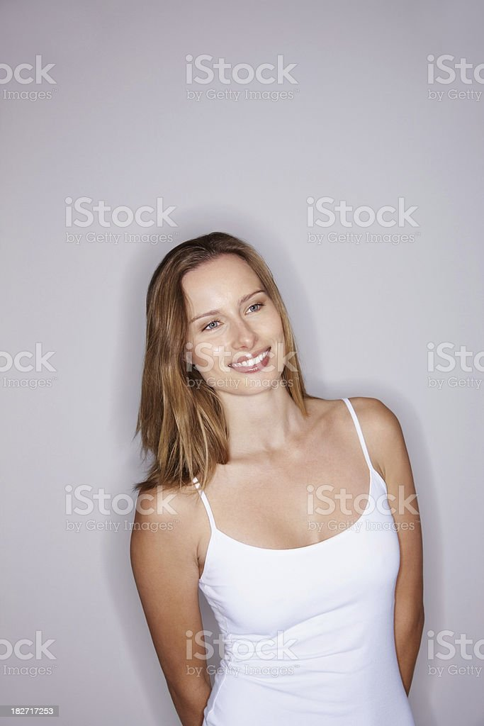 Casual woman in white standing against a gray background royalty-free stock photo