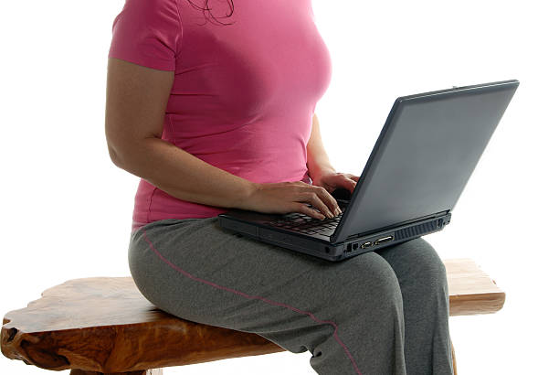 Casual woman sitting on bench with laptop stock photo