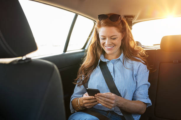 Casual woman using smartphone in car Smiling casual woman sitting in back seat using mobile phone. Cheerful young woman reading messages in smartphone while sitting in a taxi. Attractive girl with red hair wearing blue shirt in car using cellphone. passenger stock pictures, royalty-free photos & images