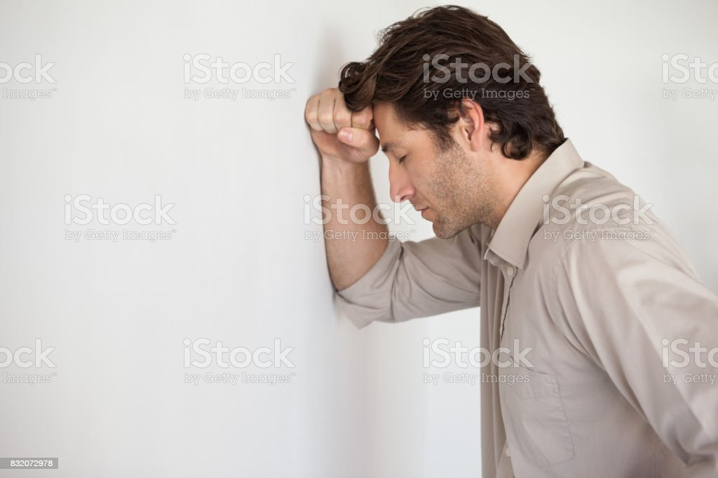 Casual worried businessman leaning head on wall stock photo