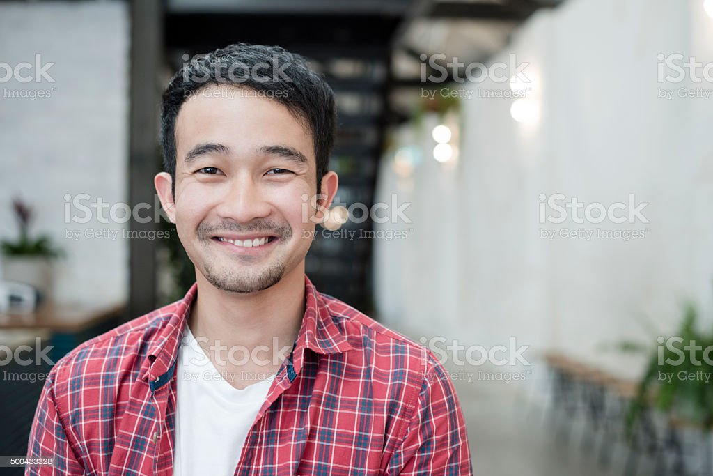 Casual young Asian businessman smiling towards camera, portrait stock photo