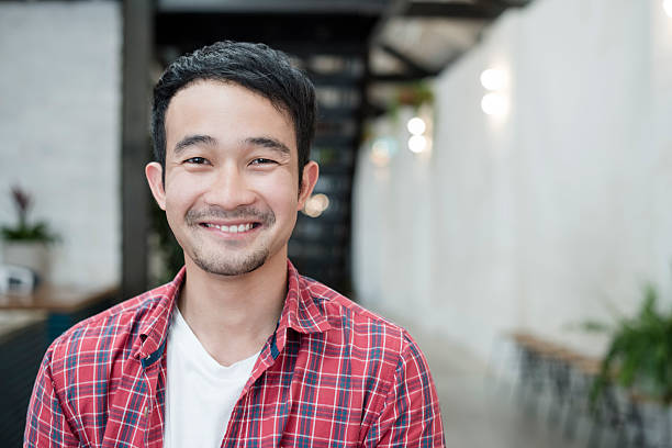 casual young asian businessman smiling towards camera, portrait - 25歲到29歲 個照片及圖片檔