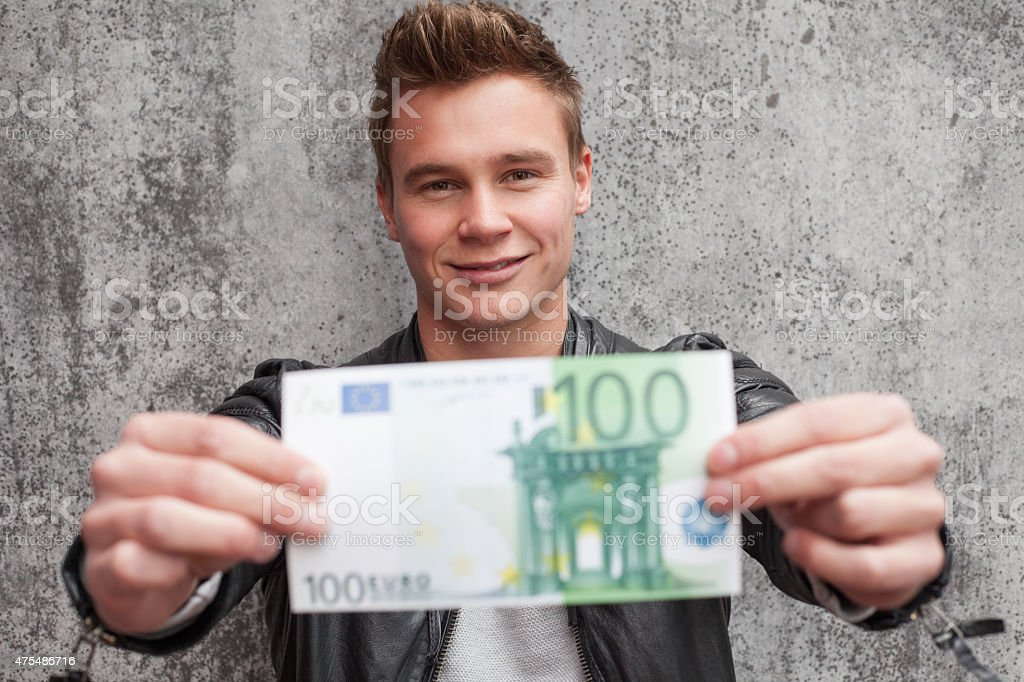 Casual young guy holding 100 euro note stock photo