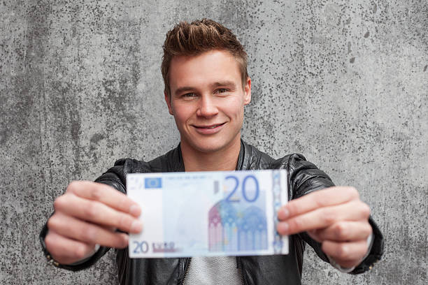 Casual young guy holding 20 euro note stock photo