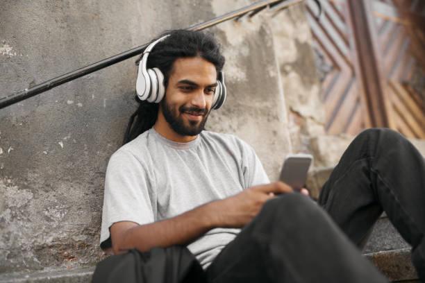 lässige junge hipster mit dreadlocks holding-handy musik hören. - geräusche app stock-fotos und bilder