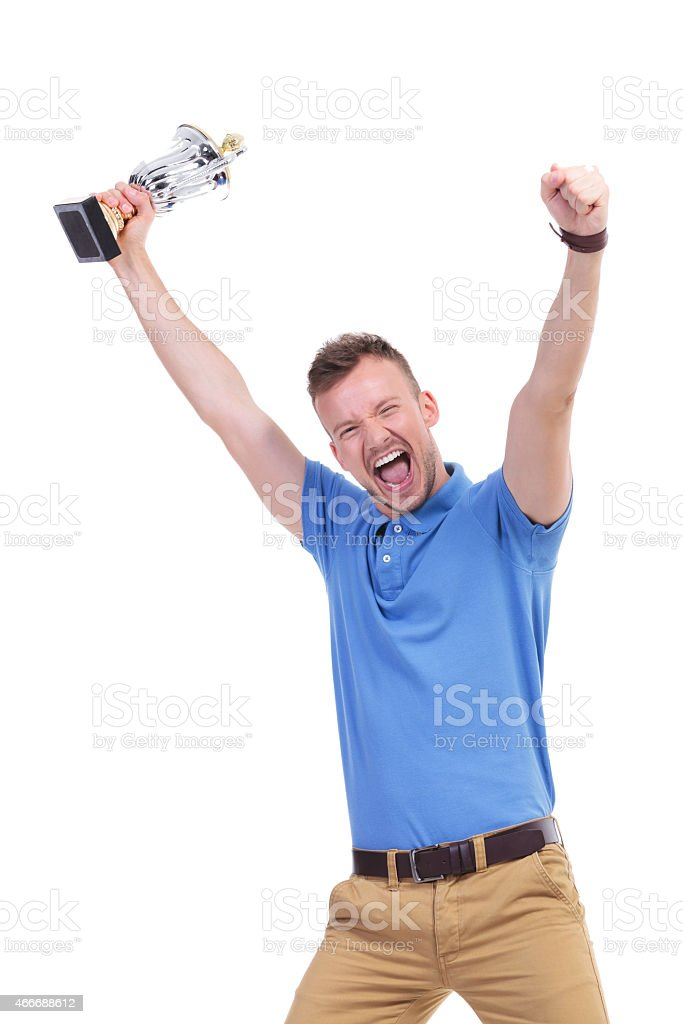 casual young man cheers with trophy in hand stock photo